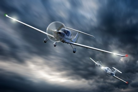 Two small aircraft in a dog fight, chasing each other in the sky photo