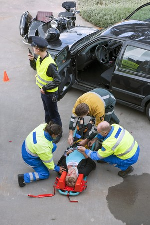 First aid team of paramedics, firefighter and police providing assistance to a severely wounded woman after a car crash photo