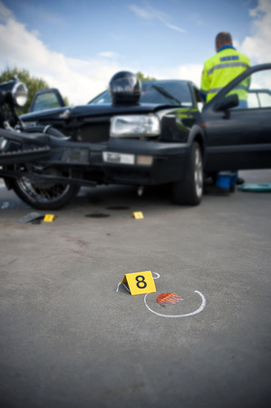 involving: Forensics placard number 8 at an accident site, involving a motorcycle and a private vehicle next to a piece of broken glass in shallow Depth of Field Stock Photo