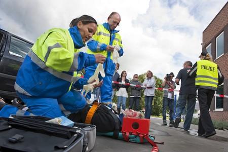 primeros auxilios: Param�dicos tiende a los primeros auxilios de una mujer lesionada en una camilla en la escena de un accidente de coche, mientras que una mujer polic�a es escolta de un espectador hacia la cinta de cord�n, siendo filmada por un hombre de la c�mara