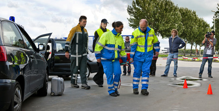 Trauma team in action at the scene of a car crash, carrying an injured driver away on a stretcher Stock Photo - 7846266