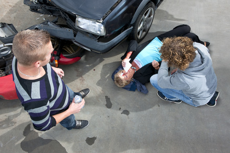 bystanders: Bystanders providing first aid to an injured woman at the scene of a car crash