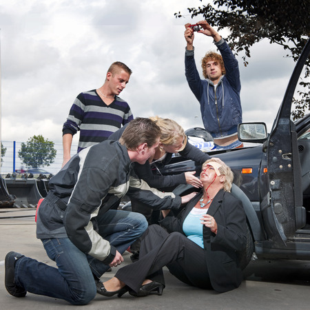 picture person: Bystanders checking up and providing first aid to an injured bleeding driver after a car crash. A man is taking pictures