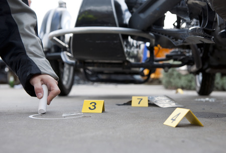 evidence: Forensics at the site of a car crash, with a policewomans hand drawing a circle with chalk around a piece of glass