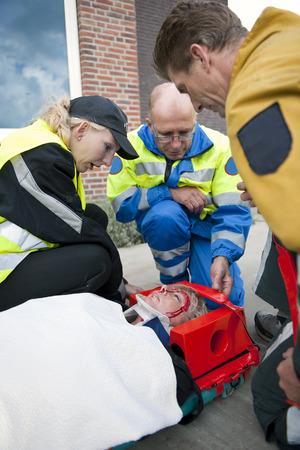medical attention: Equipo de trauma, proporcionar atenci�n m�dica a una mujer herida en una camilla llevando una llave de cuello