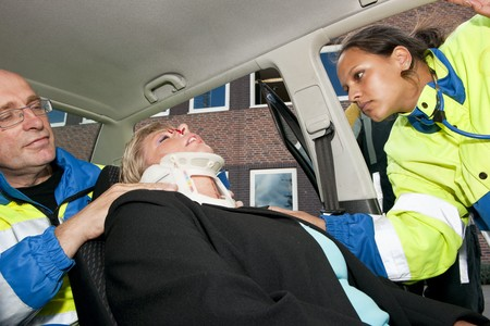 Paramedics placing a neck brace on an injured woman inside her car after a car crash