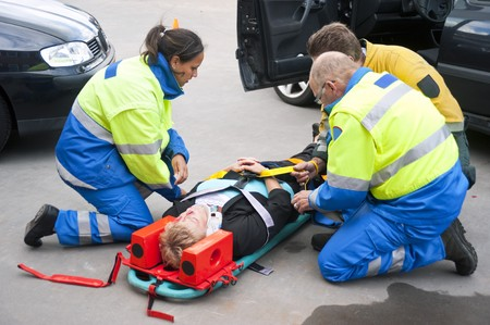 accident patient: Paramedics and a fireman strapping a wounded woman  with a neck brace on a stretcher