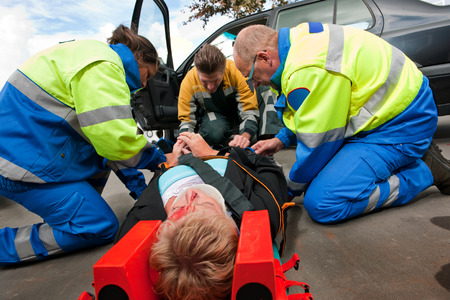 Paramedics and a fireman strapping a wounded woman  with a neck brace on a stretcher photo