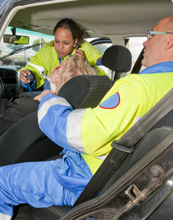 Paramedics providing first aid to an injured woman in a car Stock Photo