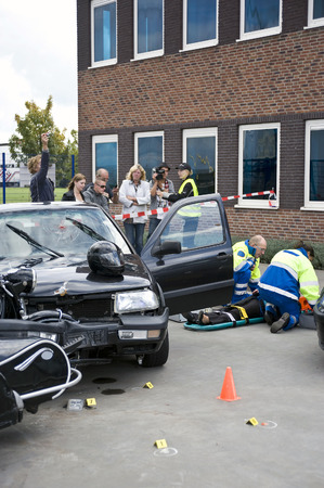 bystanders: bystanders are looking at a victim of a care accident. Stock Photo