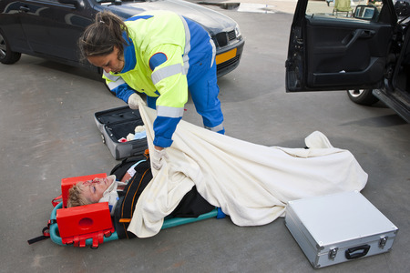 Female paramedic putting a blanket over an injured woman on a stretcher photo