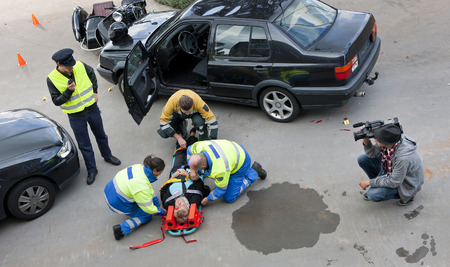 collision: A Multi-disciplinary rescue team, consisting of paramedics, fireman and a police officer tending to the victim of a car crash