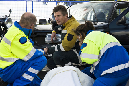 ambulance car: fireman and paramedic discussing the course of action,  carring for an woman ad the side of a car crash Stock Photo