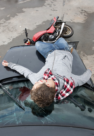 Motorcyclist is being hit by a car, and lies unconsciously on the smashed windscreen, bleeding heavily photo