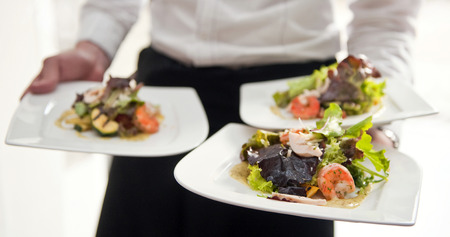 serving food: Waiter, carrying three plates with a rich salad