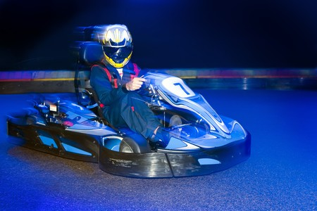kart: Go-cart driver during a lap on an indoor carting circuit Stock Photo