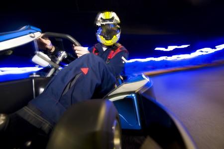 Racing driver leaning towards the corner in a go-cart at high speed on an indoor race track