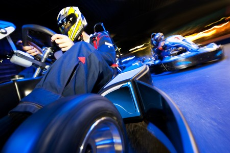 battling: Two go-cart drivers battling in a competitive race on an indoor circuit