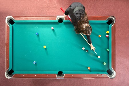 Pool table with a girl playing, seen from above photo