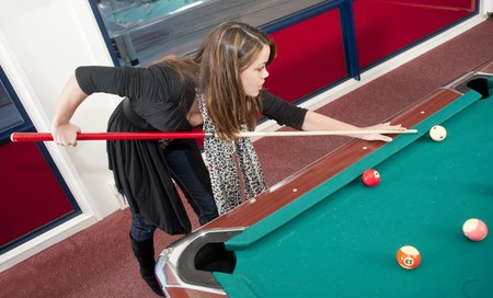 billiards room: Young woman playing pool Stock Photo