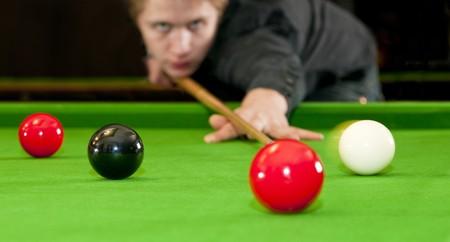 snooker room: Snooker giocatore immissione la bilia per un colpo sul nero, mentre colpisce la palla rossa (messa a fuoco selettivo e sfocatura di movimento) Archivio Fotografico