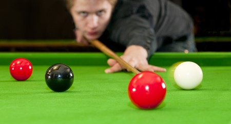 snooker room: Snooker player placing the cue ball for a shot on black, whilst hitting the red ball (Selective focus and motion blur)