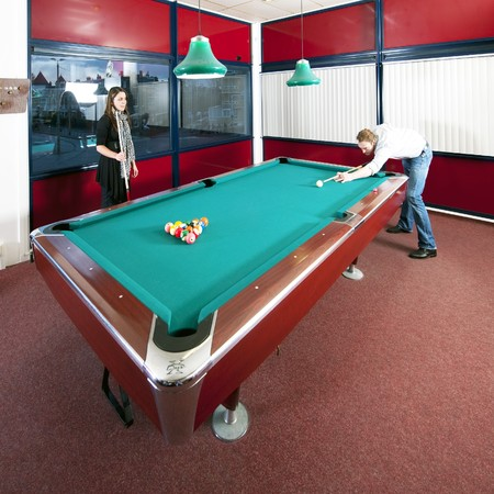 Two people playing pool in a room with a view on an city skyline at dusk Stock Photo - 8281429