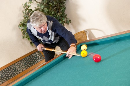 billiards rooms: Senior man playing carambole billiards