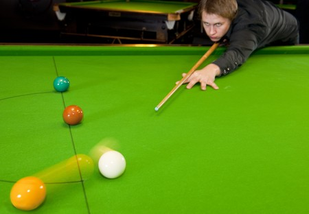 billiards room: Young snooker playing shooting the cue ball (selective focus on cue tip) Stock Photo