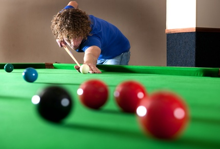 aligning: Snooker player taking a long shot across the table Stock Photo