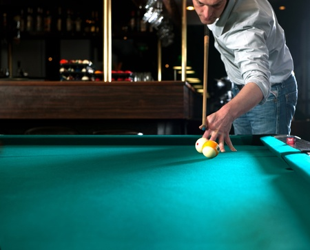 dimly: Pool player during a massee shot in a dimly lit bar