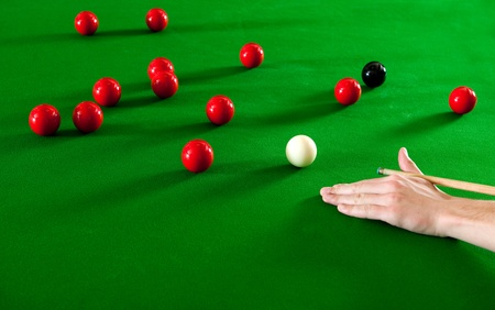 cue stick: Hand, supporting a cue stick on a snooker table