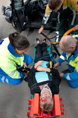 Paramedics and a fireman strapping an injured woman to a stretcher, seen from above photo