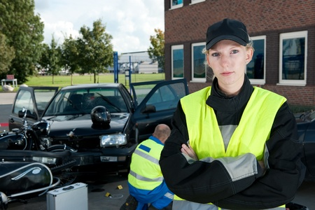 motorcycle accidents: Police woman posing on the site of a car crash, with a paramedic working in the background