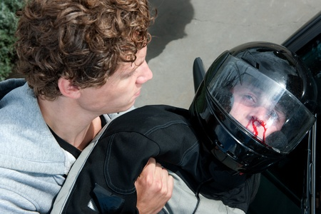 motorist: Gruesome image of a bystander lifting the lifeless body of a motorist after a car crash Stock Photo