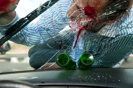 drinking and driving: Wounded pedestrian with his head on the smashed windscreen of a car, with two empty beer bottles on the dashboard - the effects of drinking and driving