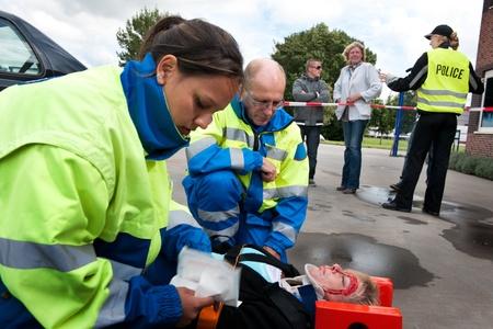 Paramédicos proporcionar primeros auxilios a una mujer lesionada con policía y transeúntes en segundo plano Foto de archivo - 8523264