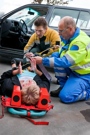 Paramedic and firefighting providing first aid to an injured woman on a stretcher photo