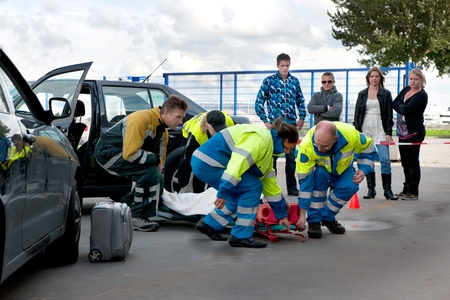 A team of emergency medical services at work, lifting an injured woman on a stretcher, to carry her away photo