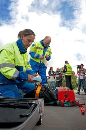 Paramedici die neigt naar de eerste hulp van een gewonde vrouw op een brancard op de plaats van een auto-ongeluk, terwijl een politie-vrouw met de omstanders achter de cordon tape praat, gefilmd door een camera man Stockfoto
