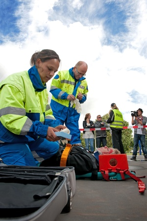 Paramedics tending to the first aid of an injured woman on a stretcher at the scene of a car crash, whilst a police woman talks to the bystanders behind the cordon tape, being filmed by a camera man photo