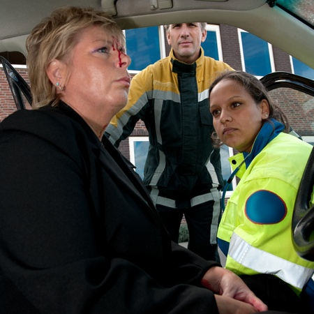 Injured woman in shock behind the wheel of her car, with a paramedic and fireman watching over her photo