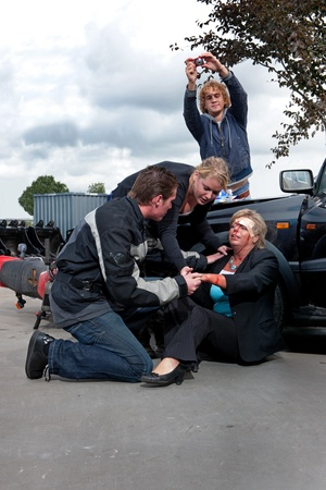 bystanders: Bystanders checking up and providing first aid to an injured bleeding driver after a car crash. A man is taking pictures as amateur journalist for social media networks