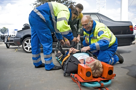 Une équipe des services d'urgence médicale au travail, straping un conducteur blessé sur une civière Banque d'images - 8727879