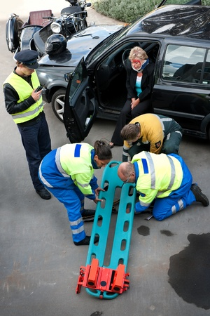 Emergency Medical Services team preparing a stretcher with head block for an injured driver photo