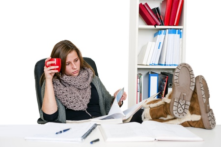 Young female student, dilligently reading her notes whilst studying with her feet on the desk and a cup in her hand, looking serious Stock Photo - 8728032