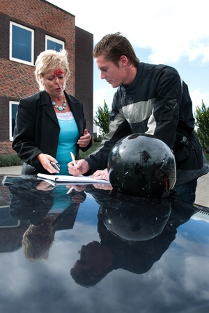 motorist: Motorist and a female driver discussing an insurance form after a  collision between a motor and an vehicle Stock Photo