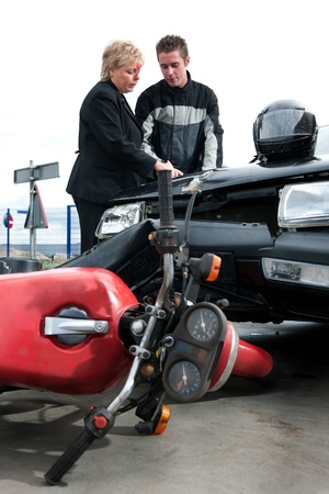 motorist: Motorist and a female driver discussing insurance issues after a frontal collision between a motor and an vehicle