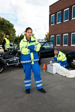 Portrait of an asian paramedic, posing in front of a car crash site photo