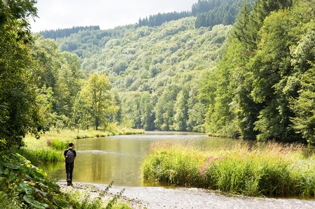 A hiker walking along a river in the Ardennes mountain range on a sunny, late summer, day. photo